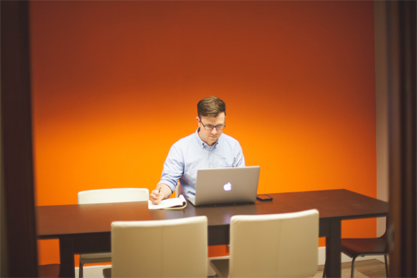 man at a desk with a macbook in an orange room