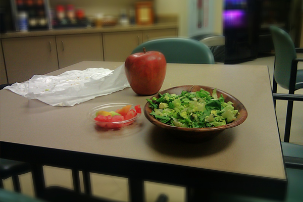 salad and an apple on a table in a breakroom