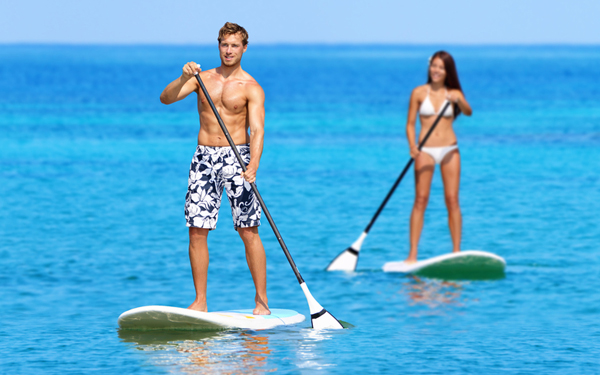 man and woman on stand-up paddle boards