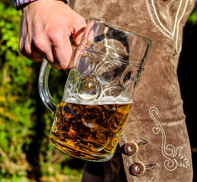 man holding a large glass beer stein halfway full