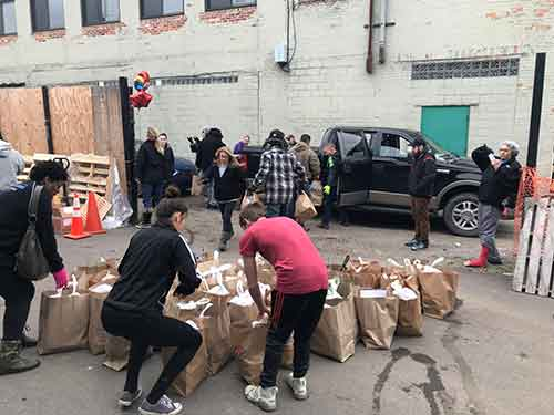 Volunteers collecting food for the homeless in brown bags in an alley