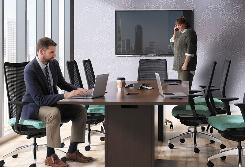 office meeting room, with desk, tv and two workers