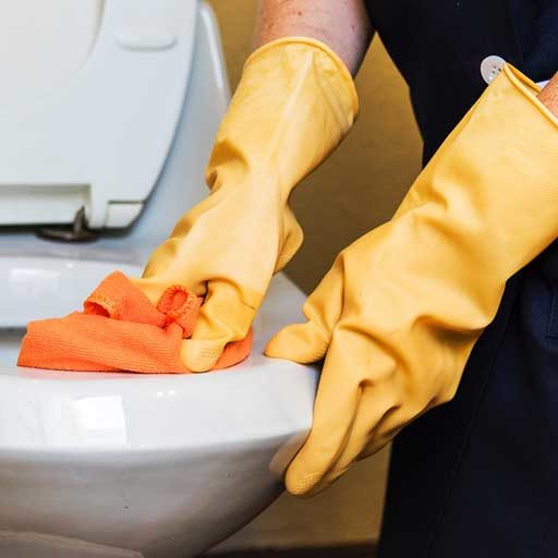 cleaning a toilet with yellow gloves and an orange rag