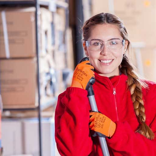 woman smiling with safety goggles and a red jacket