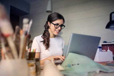 Woman with glasses at laptop at a desk with paint brushes.