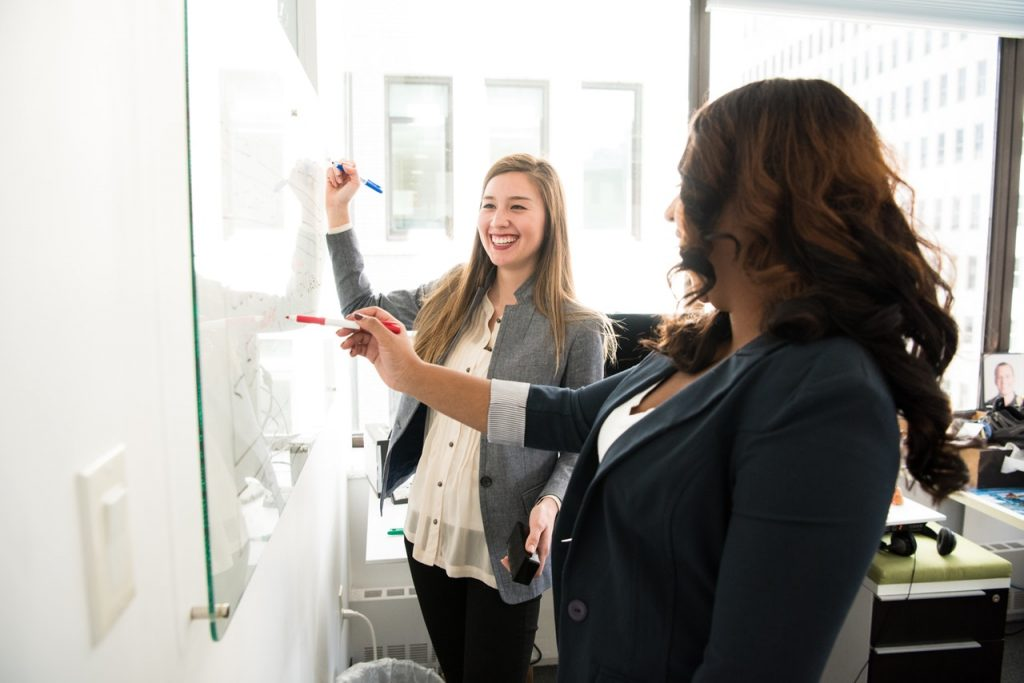 Women Working With a Whiteboard in an Office With a Window