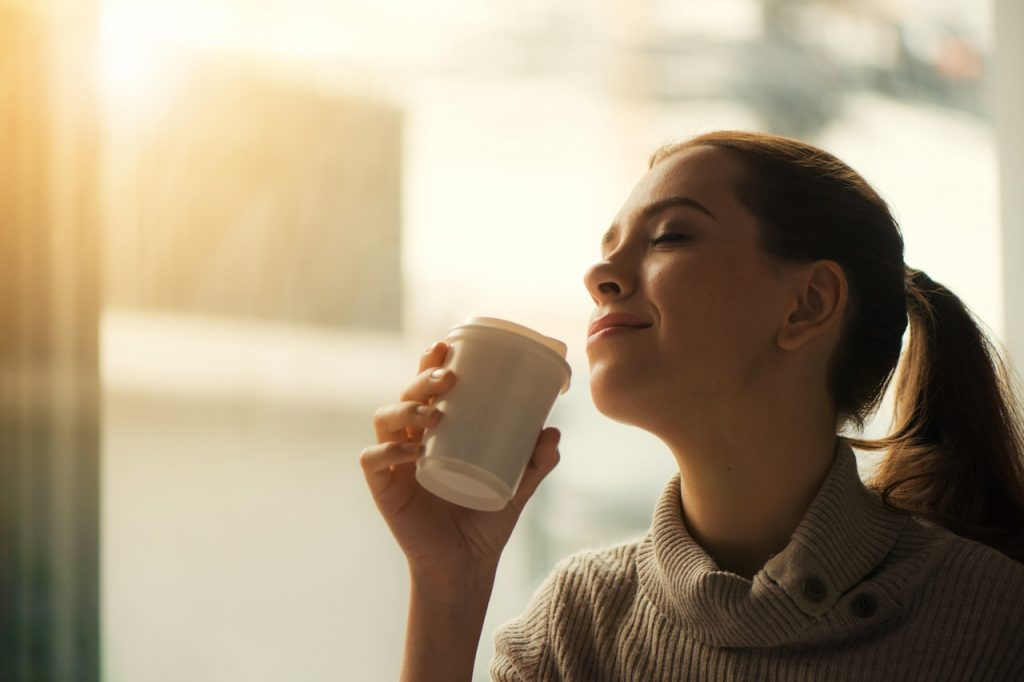 Woman Drinking Coffee, With the Sun Shining Down Outside